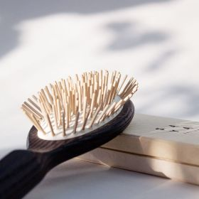 A front view of the ash hairbrush with  wooden pins.