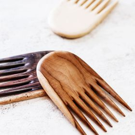The jambu hair comb in teak, tamarind and rosewood close up view on a table