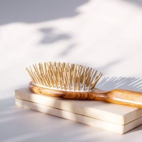 A close up side view of the olive hairbrush with  extra long wooden pins.