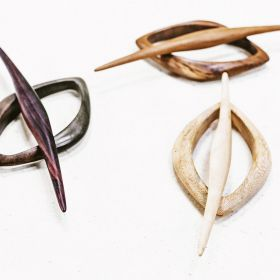 The black orchid hair slide in teak, tamarind and rosewood close up view on a table