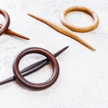 The jasmine hair slide in tamarind and rosewood close up view on a table