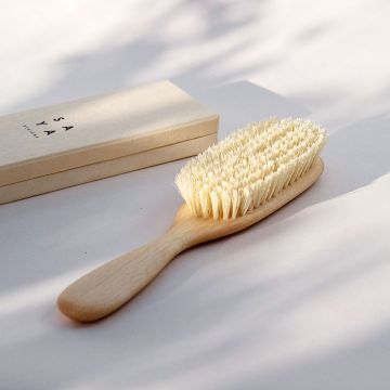 A close up of the vegan hairbrush with tampico fibres and beach wood with a box.